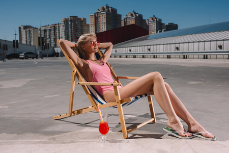 beautiful young woman relaxing in sun lounger on parking Фото со стока