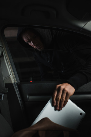 male mugger in black hoodie stealing laptop from case in car