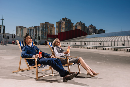 young business people relaxing on sunbeds with cocktails on parking