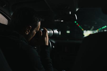vista posterior del hombre enfocado que hace la presión contra la cámara con el objeto de cristal de su coche