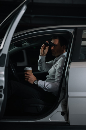 undercover male agent spying by binoculars and drinking coffee in car Stock Photo