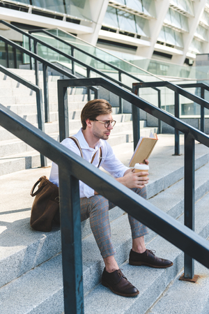 concentrated young man with paper cup of coffee reading book on stairs on city street