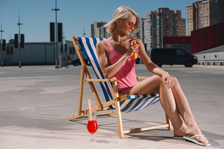 stylish young woman in pink swimsuit sitting on sun lounger and applying sunscreen lotion on parking