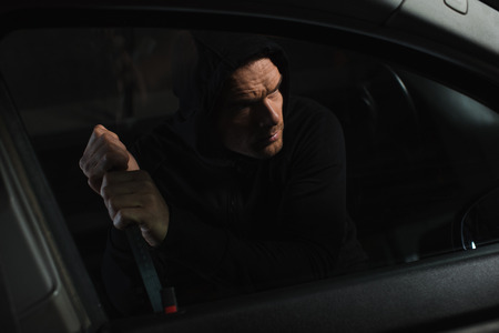 serious male robber in black hoodie intruding car by crowbar Reklamní fotografie