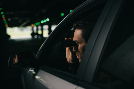 male paparazzi doing surveillance by binoculars from car