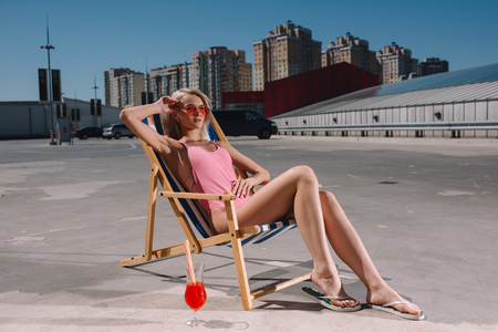 attractive young woman relaxing in sun lounger on parking