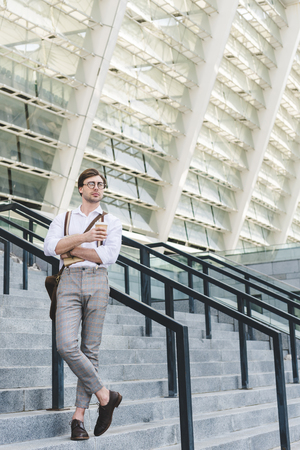 stylish young man standing on stairs in front of stadium with book and coffee to go