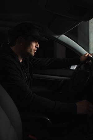 focused male paparazzi in cap driving car and doing surveillance