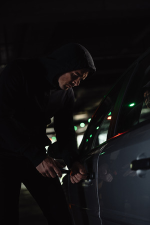 serious male robber in black hoodie intruding car by screwdriver Reklamní fotografie