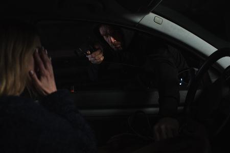 ladro maschio che mira con la pistola e ruba borsa da donna seduta in macchina