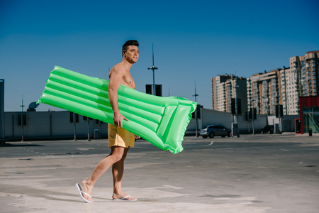 side view of young shirtless man with inflatable bed walking by parking Stockfoto