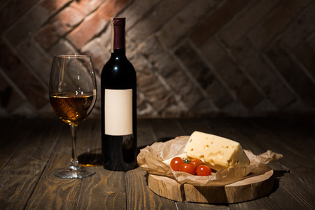 close up view of bottle and glass of wine with cheese and cherry tomatoes on baking paper on wooden decorative stump Stock Photo
