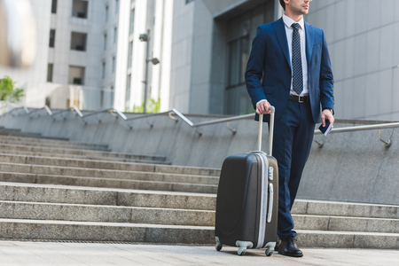 cropped shot of businessman with luggage and flight tickets walking by business district