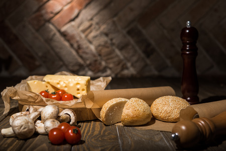 close up view of fresh cherry tomatoes, cheese, mushrooms and loafs of bread on baking paper on wooden tabletop