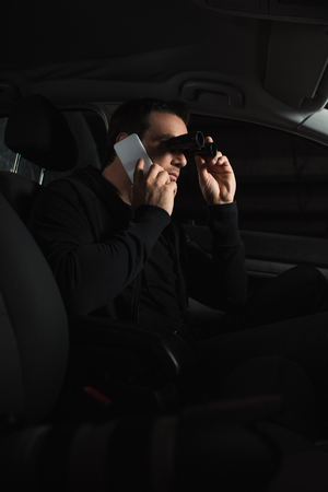man doing surveillance by binoculars and talking on smartphone in car Stock Photo