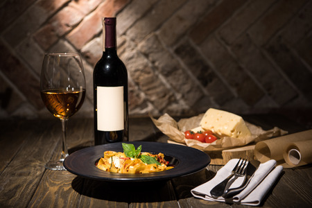 close up view of italian fettuccine pasta, wine, cheese ans cherry tomatoes on wooden tabletop