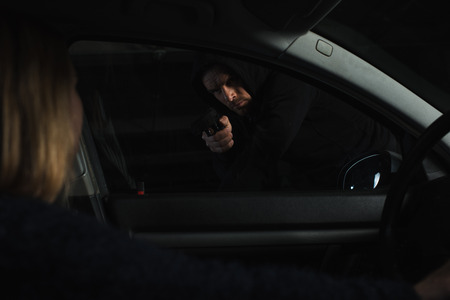 male robber in black hoodie aiming by gun on woman sitting in car