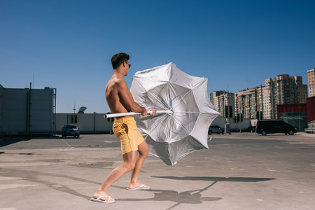 handsome young shirtless man with beach umbrella on parking Stock fotó