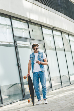 handsome young skateboarder with longboard using smartphone