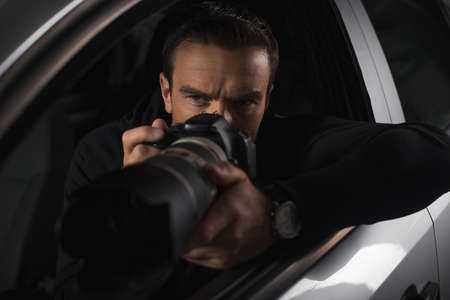 concentrated paparazzi spying by camera with object glass from his car