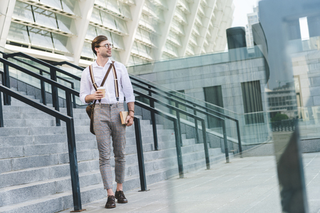 handsome young man walking in front of stadium with book and coffee to go