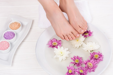 cropped shot of barefoot woman receiving bath for nails with sea salt and flowers in beauty salon Standard-Bild