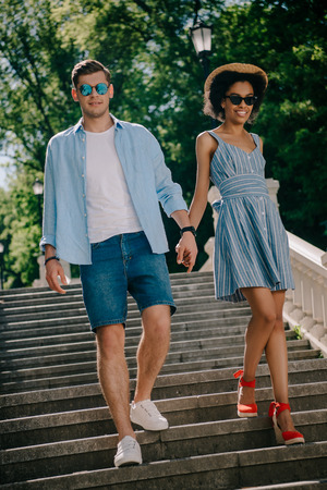young stylish couple in sunglasses holding hands and going downstairs in park Stock Photo