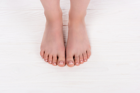 cropped shot of barefoot woman on pedicure procedure in beauty salon