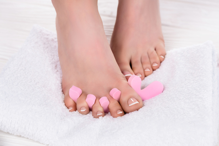 cropped shot of barefoot woman with toe finger separator on towel in beauty salon Stock Photo - 106120774
