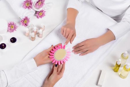 Vista superior de manicurista sosteniendo muestras de esmaltes de uñas mientras la mujer apunta con el dedo a la mesa con botellas de aceite aromático, velas, toallas, flores y esmaltes de uñas en el salón de belleza Foto de archivo