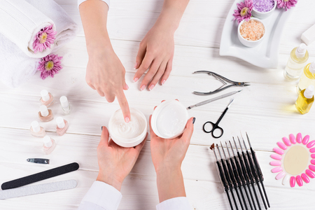 cropped shot of woman pointing on cream in hands of manicurist at table with nail polishes, nail files, nail clippers, cuticle pusher, sea salt, flowers, aroma oil bottles and samples of nail varnishes Standard-Bild - 106120546