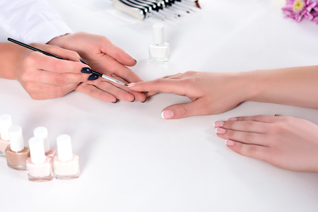 cropped image of beautician doing manicure to woman at table with nail polishes in beauty salon Stock Photo
