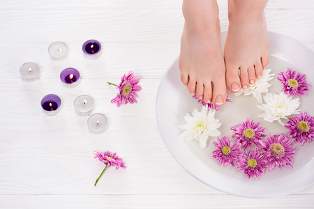 cropped shot of barefoot woman receiving bath for nails flowers near aroma candles in beauty salon 写真素材