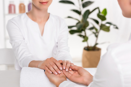 cropped image of manicurist looking at hands of woman at table in beauty salon Stock Photo