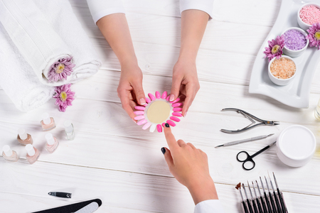 manicurist showing samples of nail varnishes to woman at table with flowers, towels, nail polishes, nail files, nail clippers, sea salt, cream, cuticle pusher and scissors Standard-Bild - 106120025