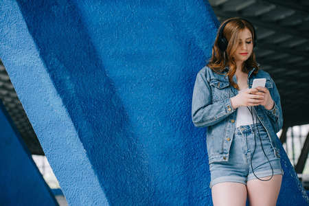 portrait of young fashionable woman in denim clothing and headphones using smartphone