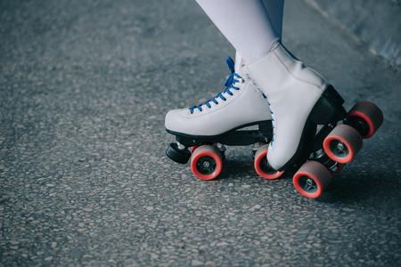 Vue partielle de la femme en chaussettes hautes blanches et patins à roulettes rétro