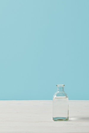 glass bottle of water on white tabletop isolated on blue