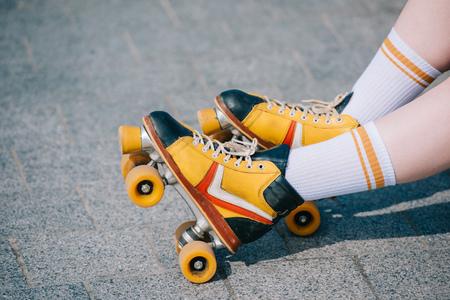 primer plano visión parcial de piernas femeninas en patines de madera Foto de archivo