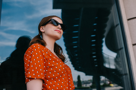 low angle view of beautiful stylish girl in sunglasses looking away on street