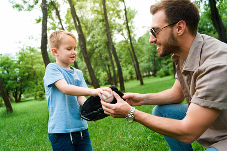 father giving son baseball ball and glove at park