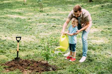 father and son watering seedling with watering can together at park