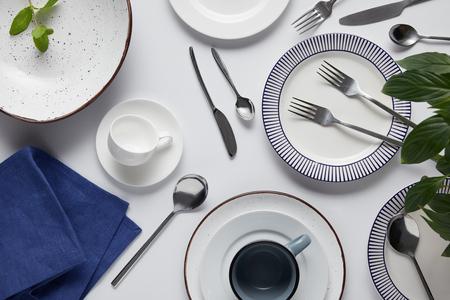 bovenaanzicht van groene bladeren, verschillende keramische platen, beker, theedoek, vorken, lepels en messen op witte tafel Stockfoto