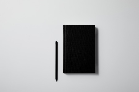 top view of black notebook with pencil on white surface for mockup Banco de Imagens