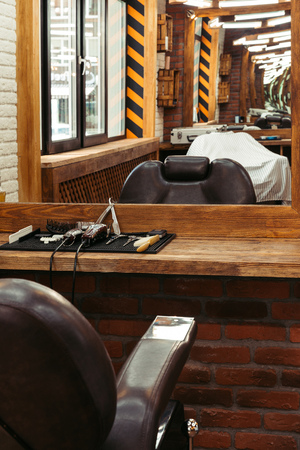 modern barbershop interior reflected in mirror and professional barber tools on wooden shelf