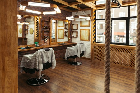 empty chairs and mirrors in modern barbershop interior 스톡 콘텐츠