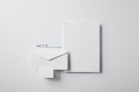 top view of layered envelope with pen, blank paper and business card on white surface for mockup Stock fotó