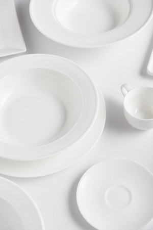 high angle view of various plates and cup on white table