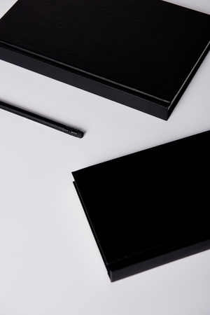close-up shot of black notebooks with pencil on white tabletop for mockup