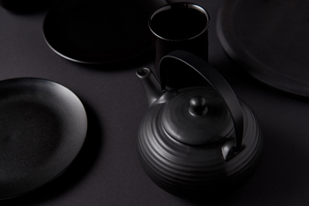 selective focus of black teapot, cup and plates on black table
